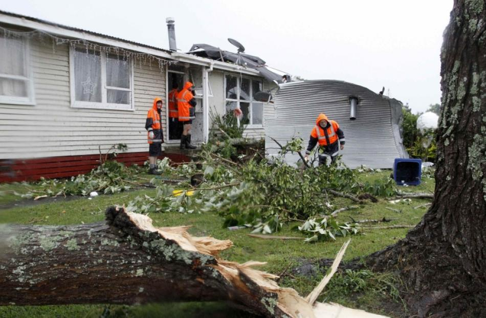 Rescue workers search amid the devastation in the suburb of Hobsonville after a tornado went...