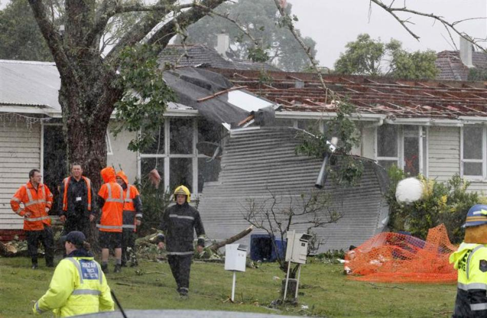 Rescue workers survey a site in the west Auckland suburb of Hobsonville after a tornado went...