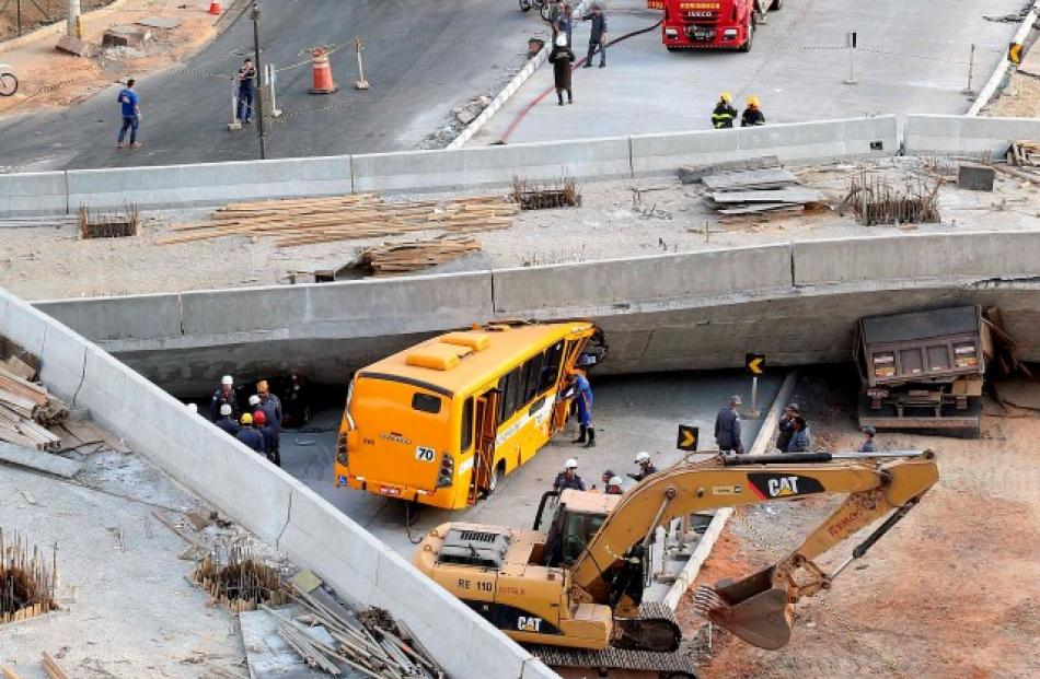 Rescue workers try to reach vehicles trapped underneath a bridge that collapsed while under...