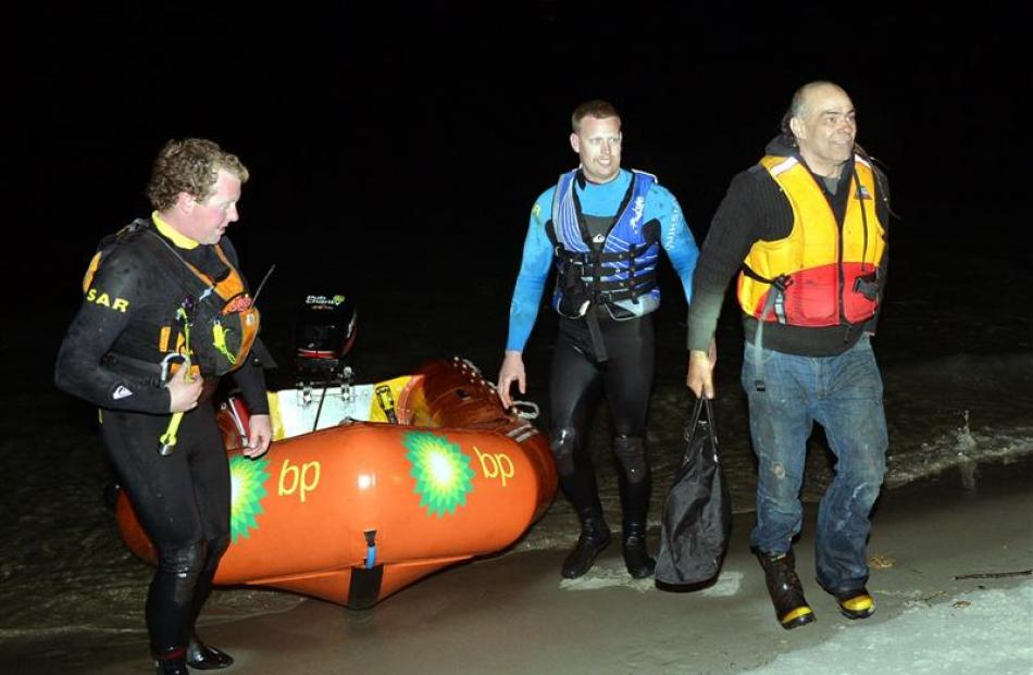 Rescued skipper Colin Webb (right) heads for high ground at Taieri Mouth last night after being...