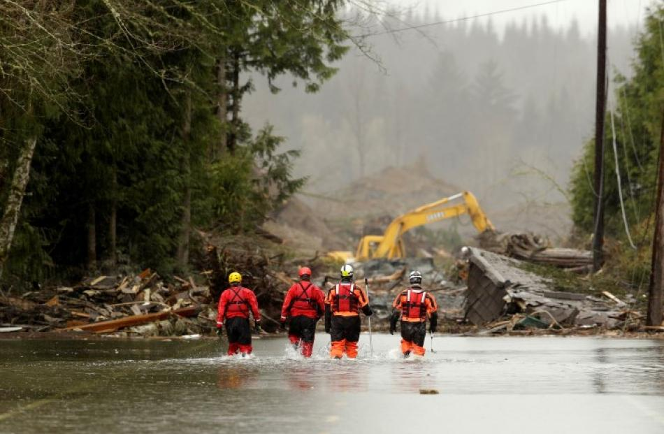Rescuers walk in floodwaters on Highway 530 as search work continues after the mudslide that...