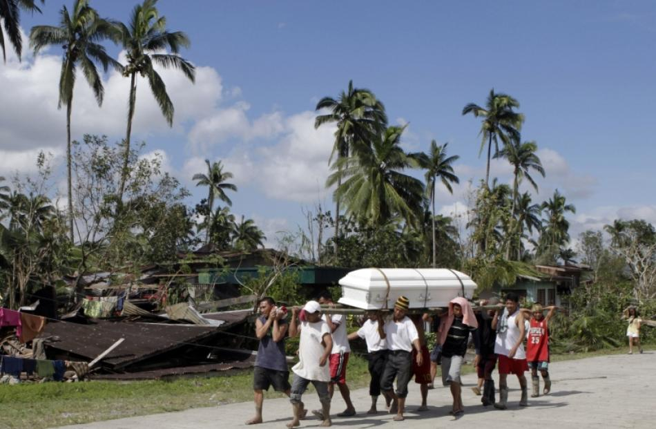 Residents carry the coffin of a typhoon victim past a destroyed house in New Bataan town in...