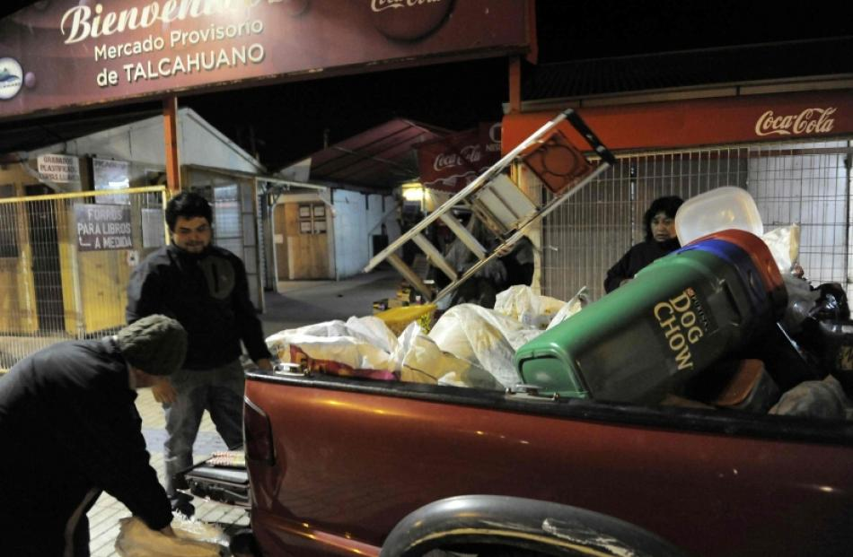 Residents take their belongings to higher ground after a Tsunami alarm at Talcahuano city, south...