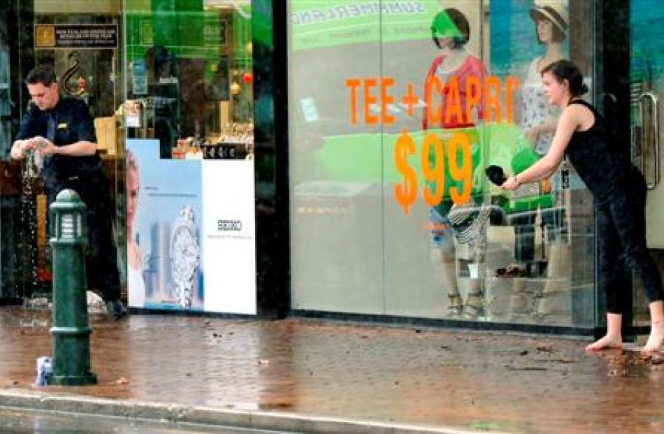 Retail staff from Daniels Gemtime Jewellers and Max Fashions mop up after flooding in George St...