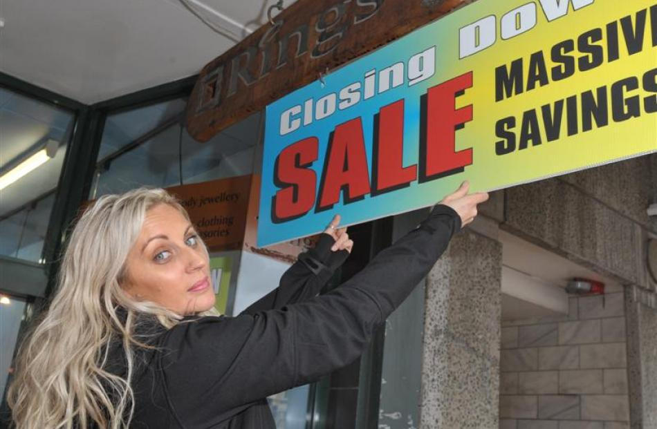 Rings N' Things manager Stacey Fraser hangs a closing  sale sign  outside the Dunedin jewellery...