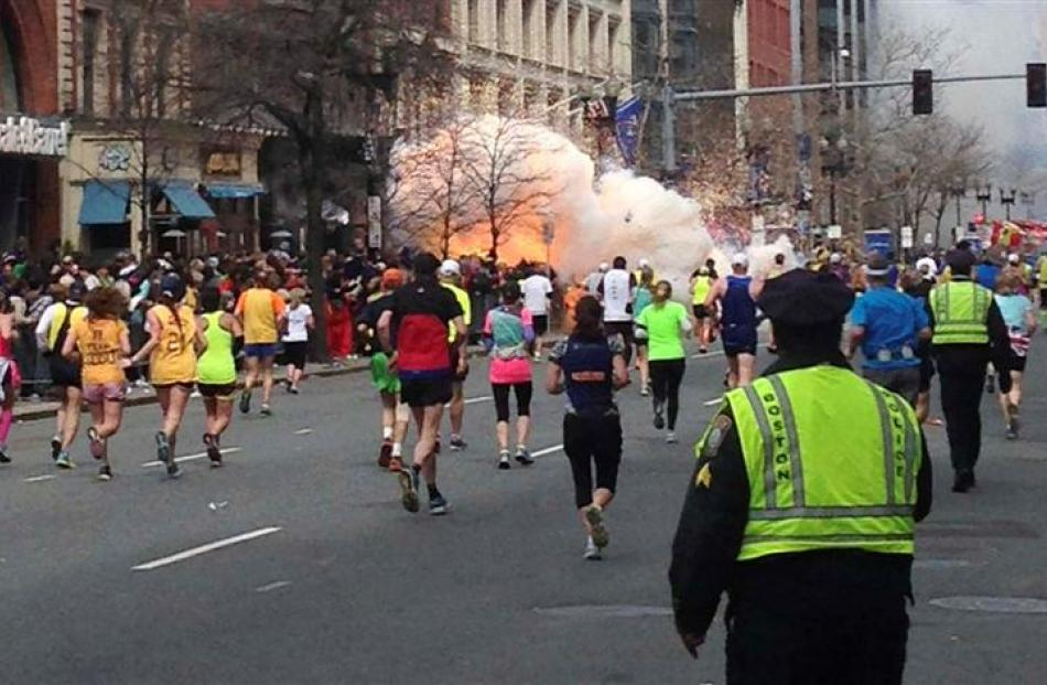 Runners continue to run towards the finish line of the Boston Marathon as an explosion erupts...