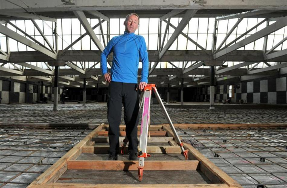 Russell Lund stands on the top floor of the Loan and Mercantile building after consent was...