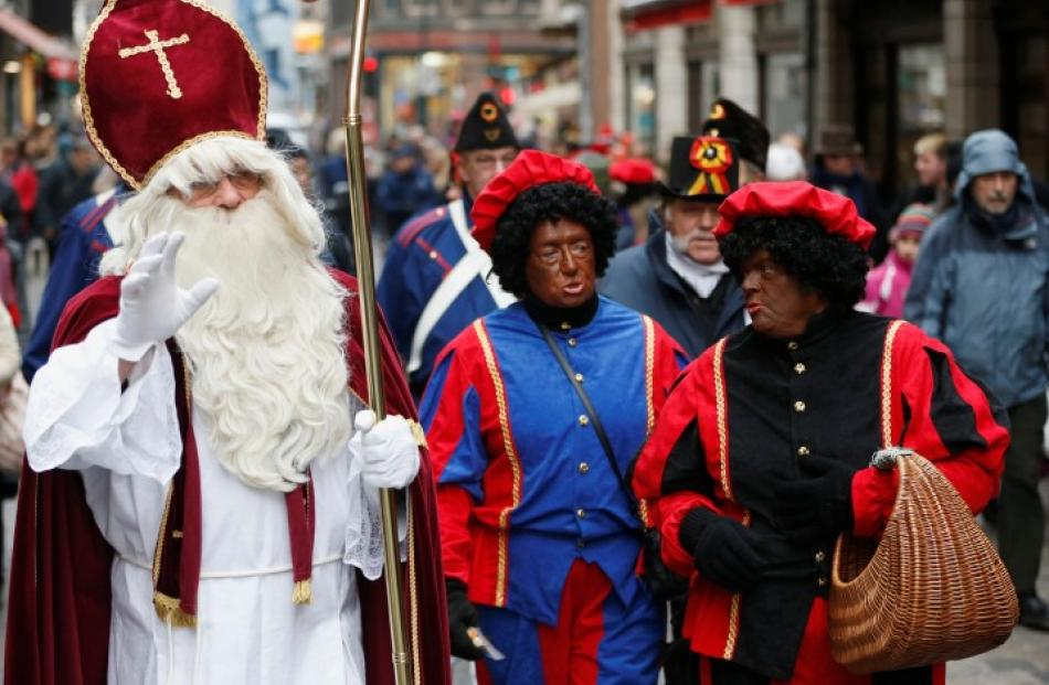 Saint Nicholas (L) is followed by his two assistants called 'Zwarte Piet' (Black Pete) during a...