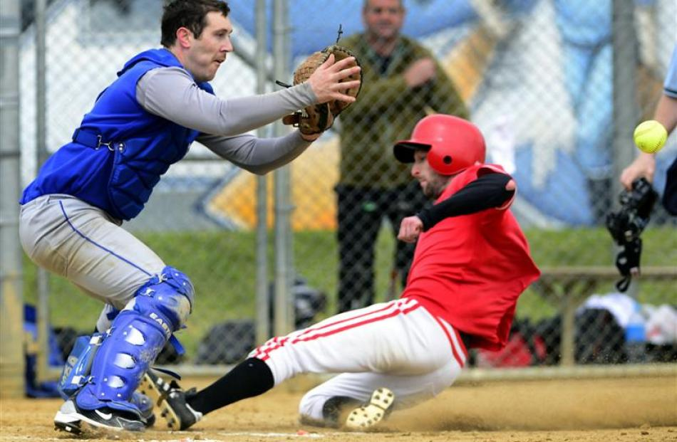 Saints catcher Michael Crowley (left) waits for the ball as Dodgers runner Josef Olson slides...