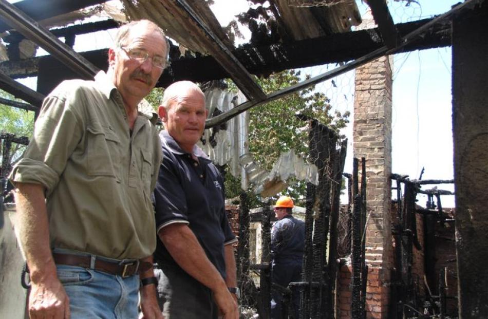 Sam Leask (left) inspects the burnt-out ruins of his childhood home in Ophir with Ken Lake, who...
