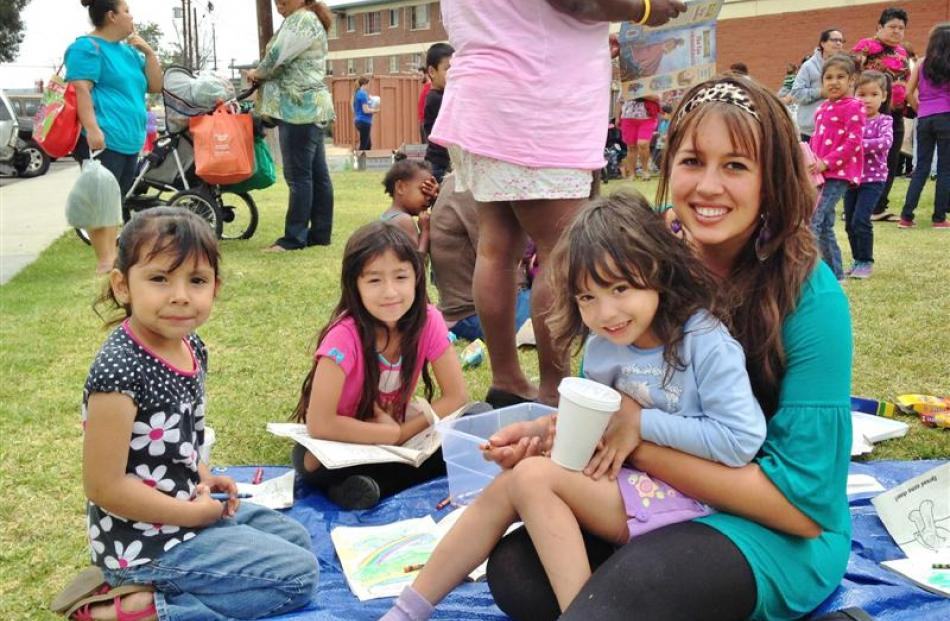 Samantha Martin (right) takes time out from her work at the Dream Center to hang out with some...