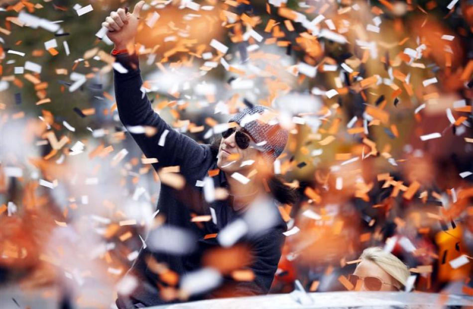 San Francisco Giants pitcher Tim Lincecum waves as he rides through confetti during a victory...