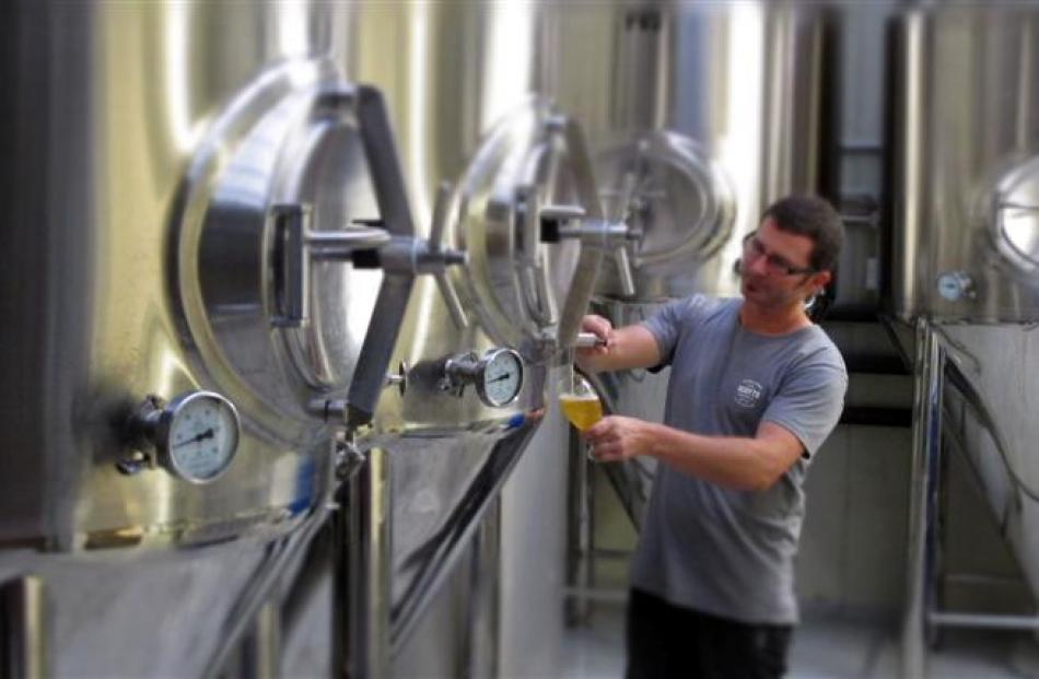 Scotts Brewing Company owner Phillip Scott pours a glass of beer at the company's Auckland...