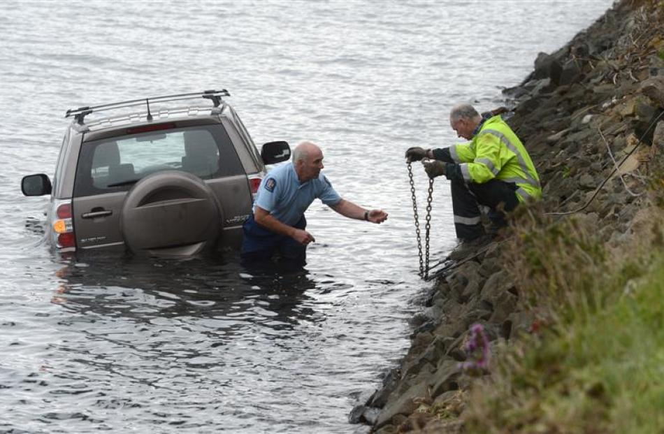 Senior Constable Paul Buchanan and Reilly's Towage and Salvage driver Max Dewar prepare to pull a...