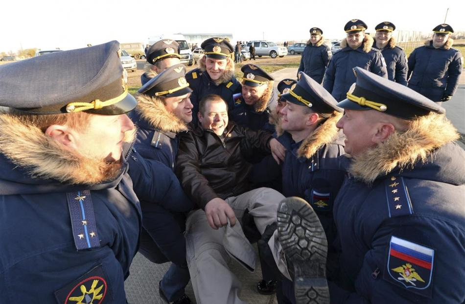 Servicemen throw a pilot in the air as they gather to welcome Russian military aircraft and...