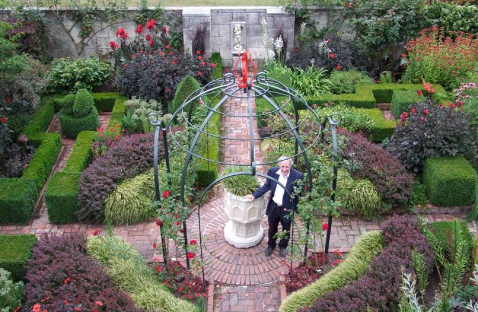 Sir Miles stands by an old font in the centre of the formal Red Garden. The use of red was echoed...