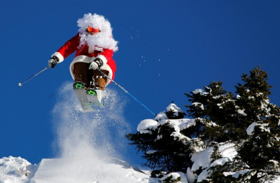 Ski teacher Alberto Ronchi makes a jump dressed as Santa Claus in Madonna di Campiglio in...