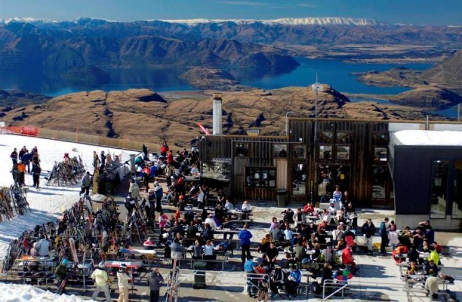 Skiers enjoy the sun outside the Treble Cone ski area base building in September 2010. Skiing is...