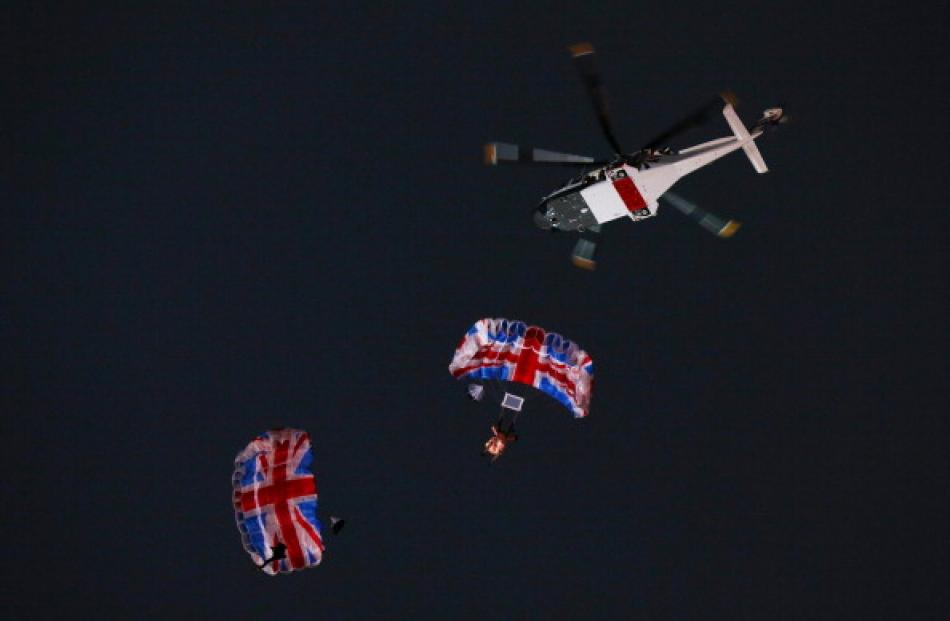 Skydivers parachute into the Olympic Stadium as part of a short James Bond film featuring Daniel...