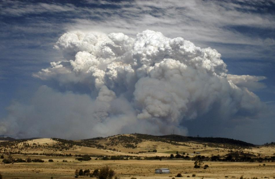 Smoke from a bushfire billows over hills near Forcett, about 25km east of Hobart. Photo by Reuters