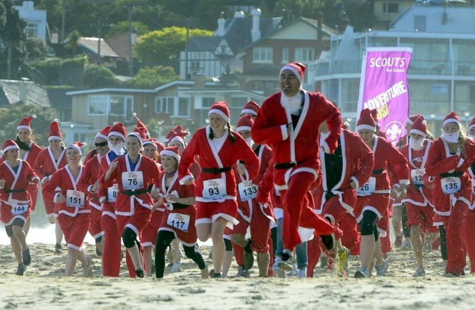 Some of the 152 participants take part in Great KidsCan Santa Run on St Clair beach in Dunedin...