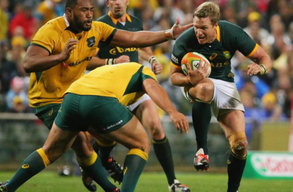 Springbok captain Jean de Villiers (R) tries to get past the Wallabies defence during their match...