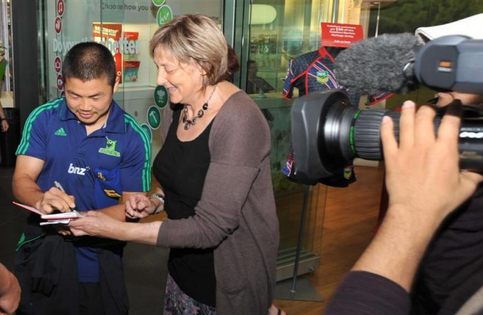 Highlanders halfback Fumiaki Tanaka signs an autograph for a fan at the Wall Street mall last...
