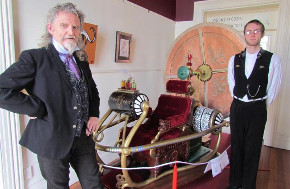 Steampunk art exhibition co-organiser Iain Clark, left, and Edward Allan with the replica of the...