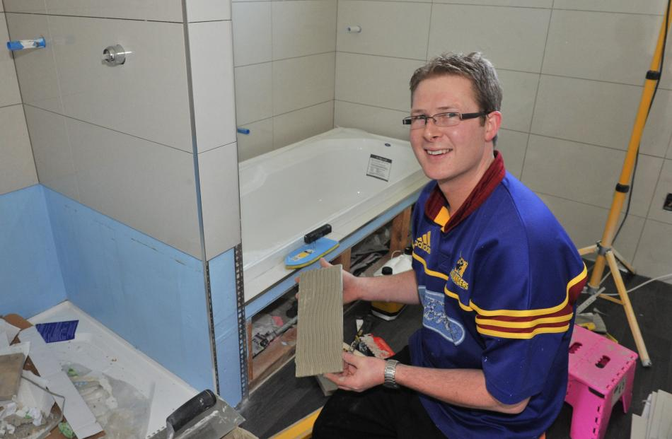 Steven Loughrey tiles the bathroom of his Mosgiel home. Photo by Linda Robertson