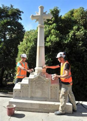 Stonemasons Wei Liu (left) and Marcus Wainwright clean up the new spire and cross installed by...