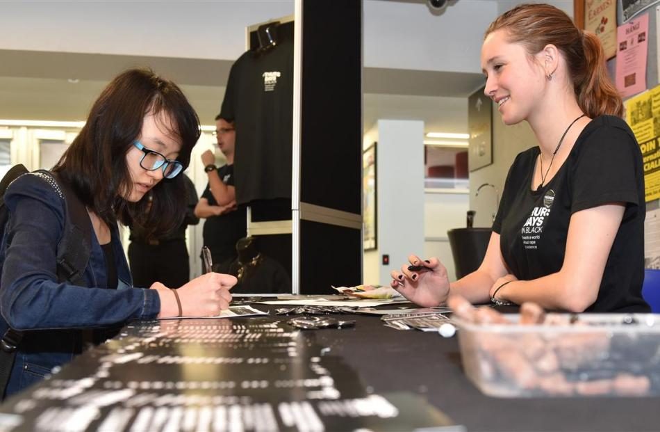 Student Qiao Zhang signs on for Thursdays in Black, a campaign against sexual violence, as Ella...
