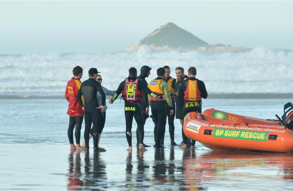 Surf life-savers and two of the four surfers rescued yesterday chat after a jet ski and the...