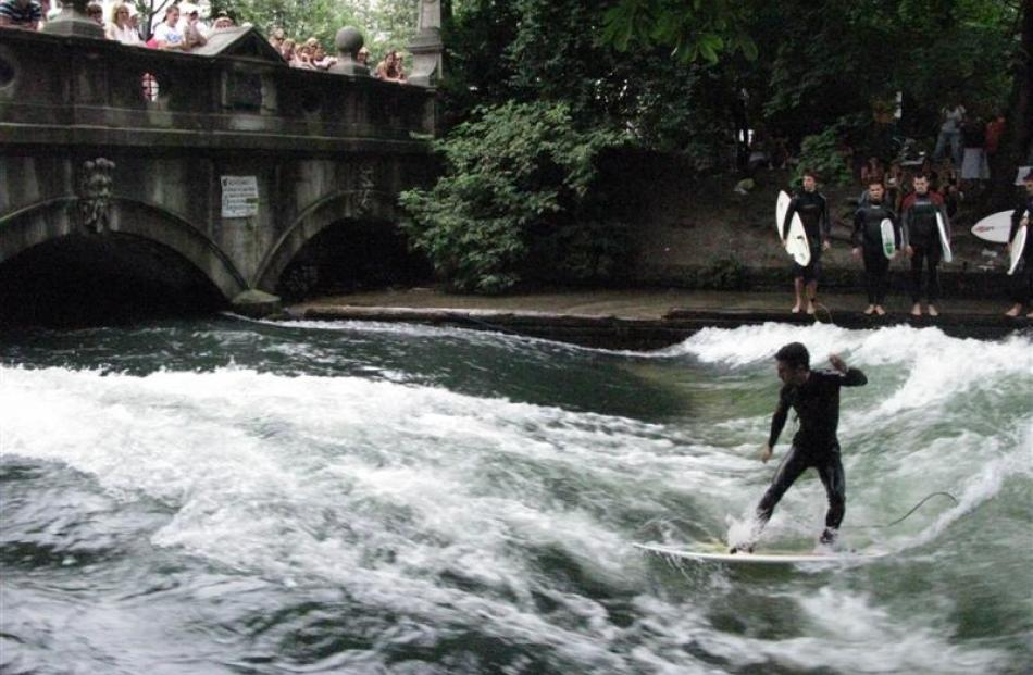 Surfers test their skills on Eisbach (Ice Creek) as it emerges from beneath Himmelreich bridge....