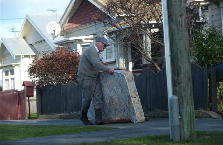 Surrey St resident Stuart Payne takes a damp mattress to a Dunedin City Council skip yesterday...