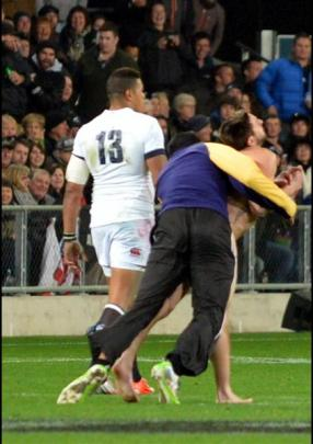 A streaker is tackled by security  worker Brad Hemopo at the All Blacks versus England test match...