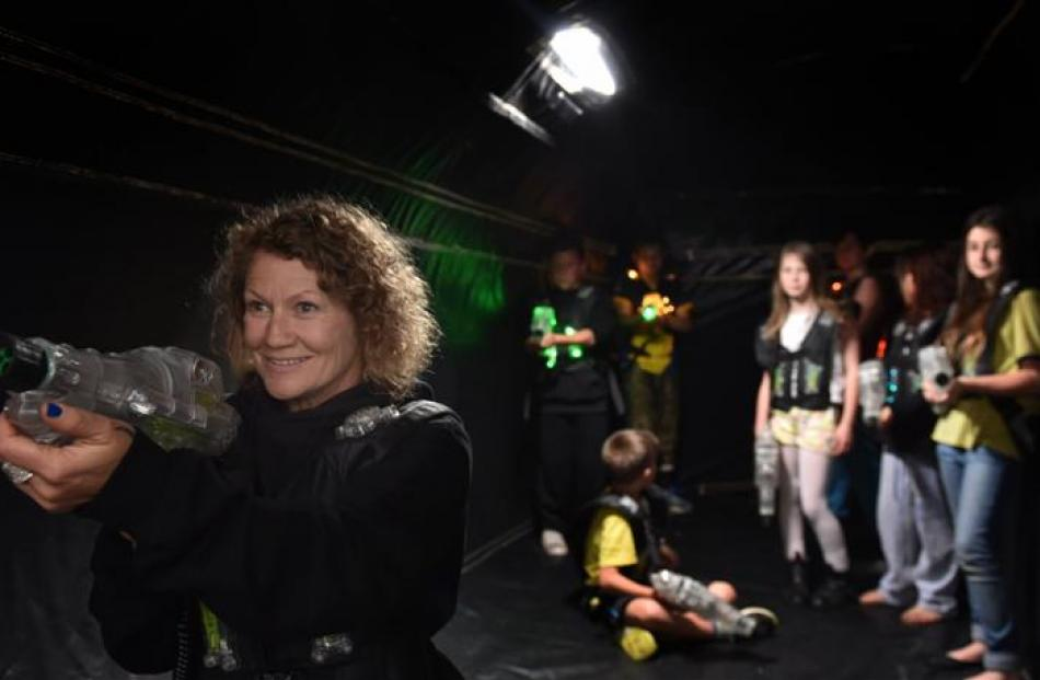 Tarn Felton aims her laser in a Megazone game tent at the Caversham  MoveMe event at Carisbrook...