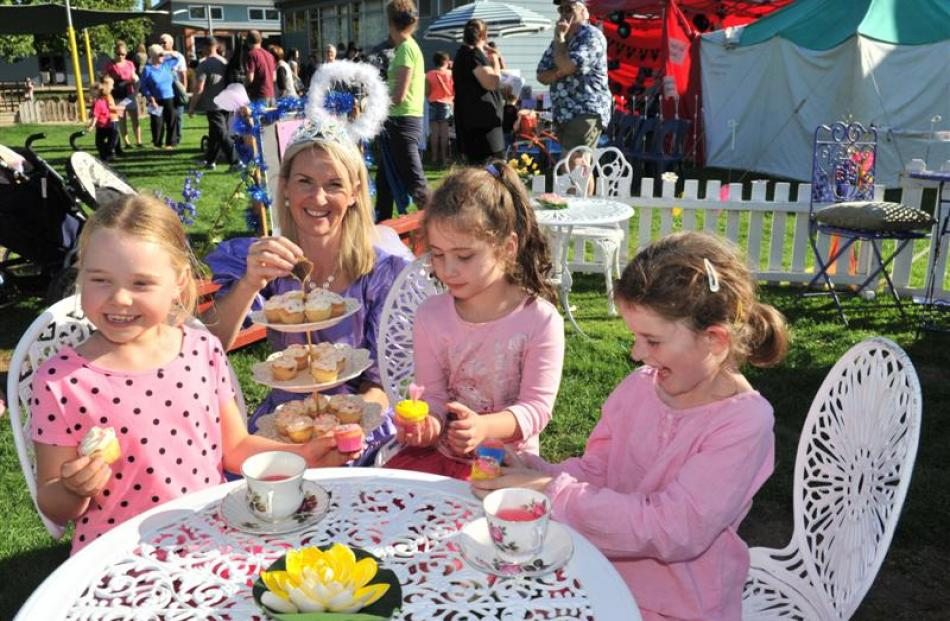 Teacher Tania Bellamy offers fairy cakes to (from left) Mia Webster, Lily Robertson and Sophie...