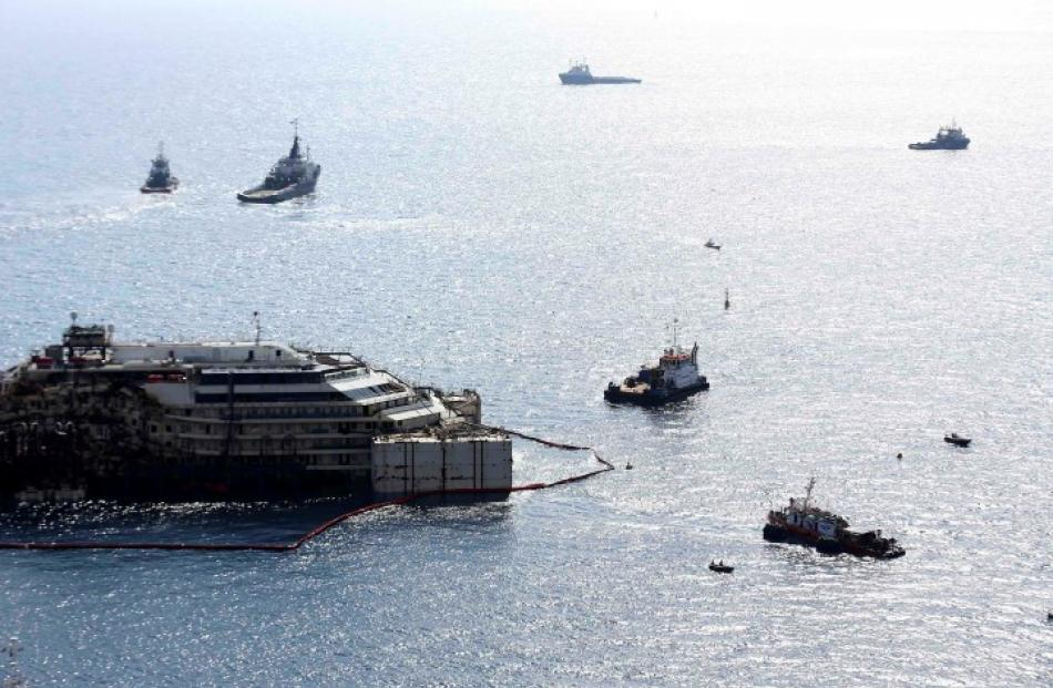 The Costa Concordia is surrounded by tugboats during the refloat operation in Giglio harbour....
