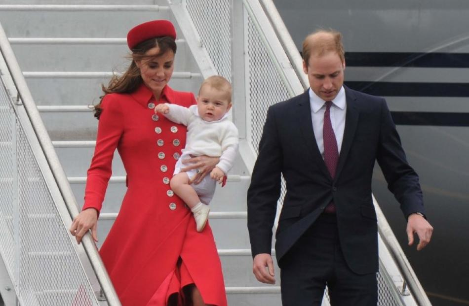 The Duke and Duchess of Cambridge, with Prince George, disembarking from the RNZAF jet after...