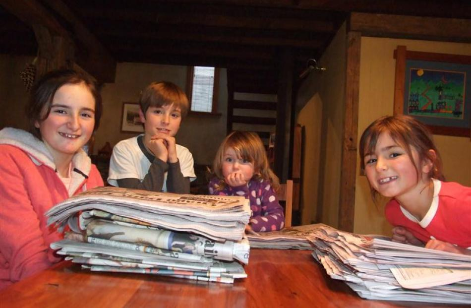 The McChlery children, of Arrowtown, with newspapers from the days of their birth throughout...
