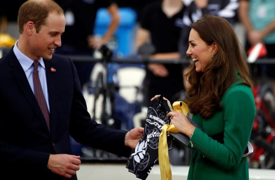 The royal couple share a laugh after being presented with a cycling jersey for their son, Prince...