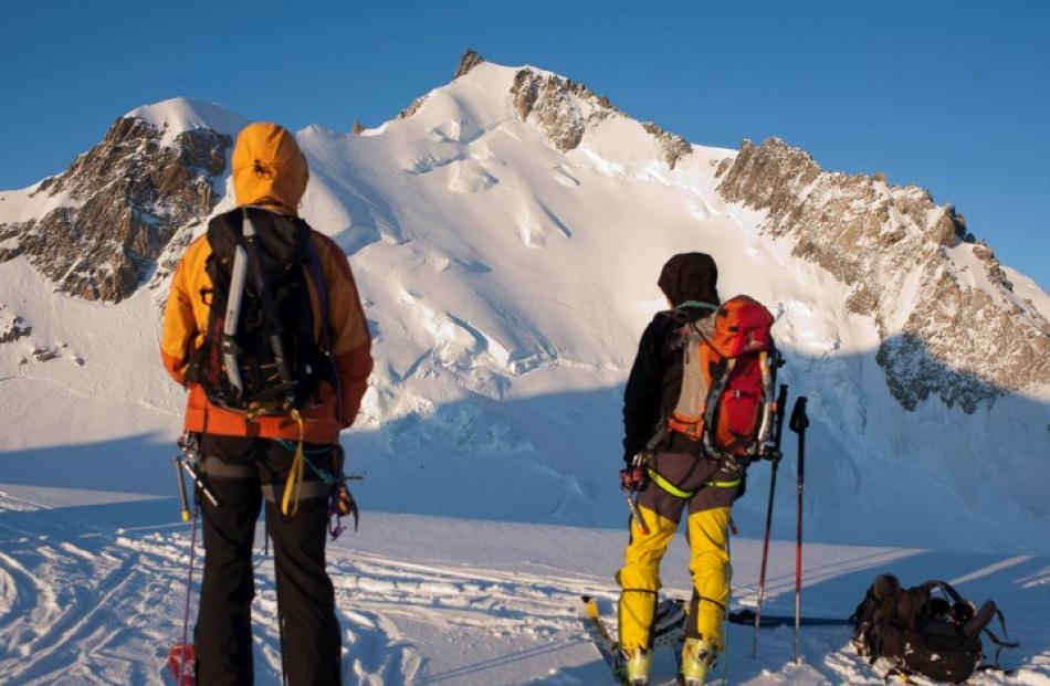 Climbers look at Mont Maudit in the French Alps, where nine people have been killed in an...