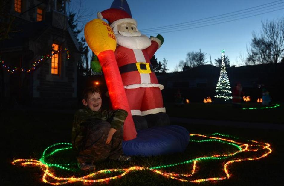 Thomas Dunn (9), of Middlemarch, sits by Santa outside St John's Presbyterian Church during the...