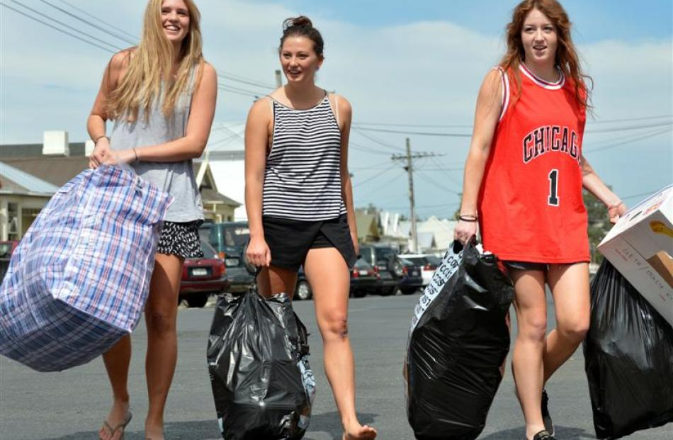Throwing trash away from their Castle St flat in Dunedin yesterday were (from left) Olivia van...