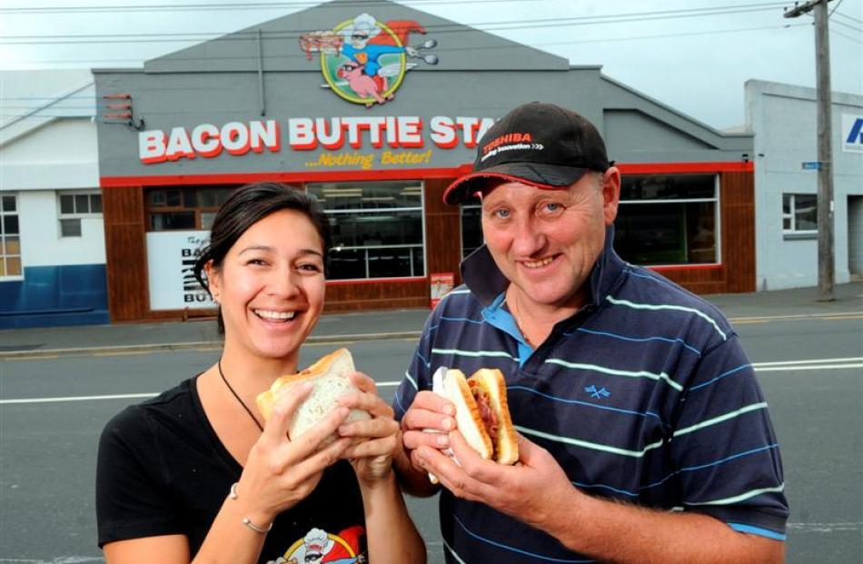 Tia Winikerei and her stepfather Mike Cornelissen enjoy bacon butties outside the Bacon Buttie...