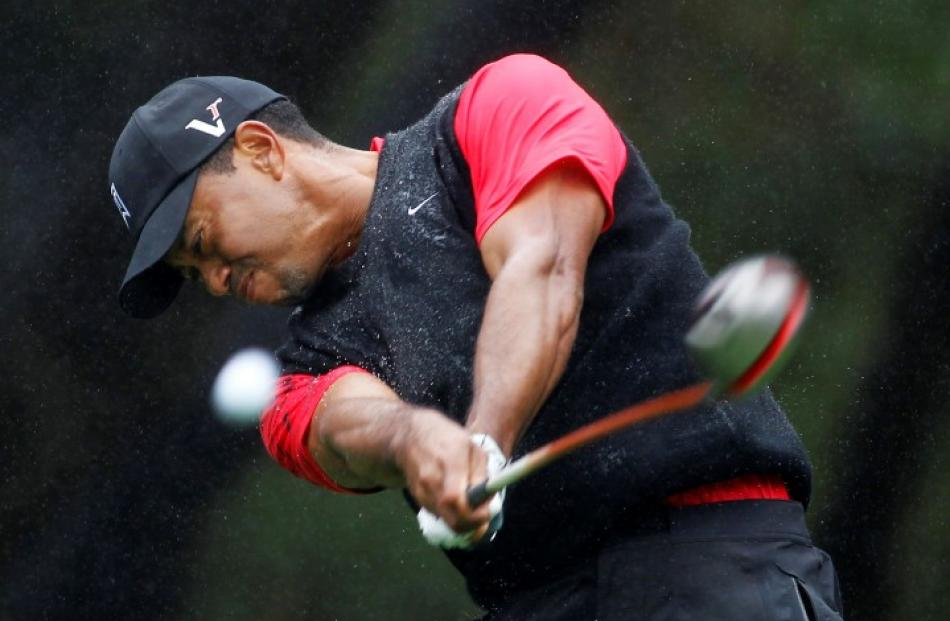 Tiger Woods tees off in the rain on the sixth hole during the final round of the World Challenge...