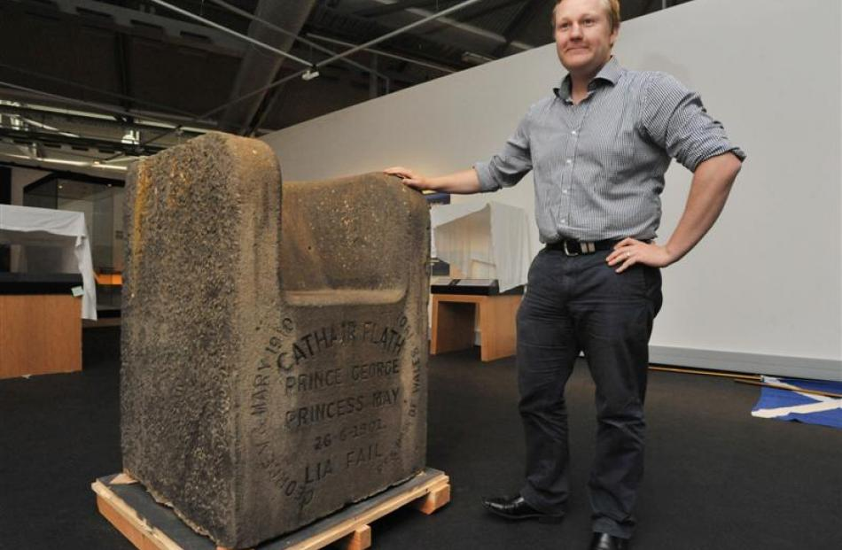 Toitu Otago Settlers Museum exhibitions developer William McKee examines a stone chair, which is...