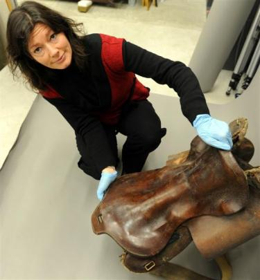 Toitu Otago Settlers Museum visitor experience manager Kirsty Glengarry holds a saddle believed...