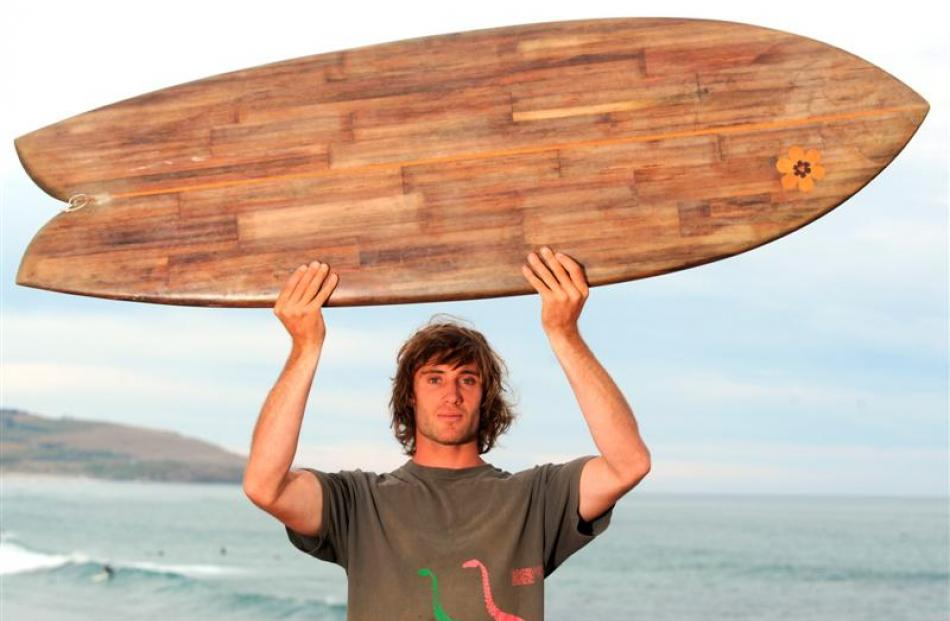 Tom Leckie with his surfboard made of flax stalks, at St Clair last night. Photo by Gregor...