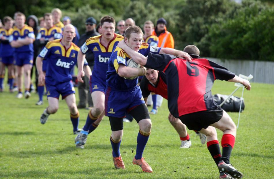 Troy Wyatt (Otago-Southland) pushes past a Canterbury player to score a try.
